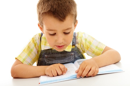 child book: Portrait of a little boy reading a book isolated on white