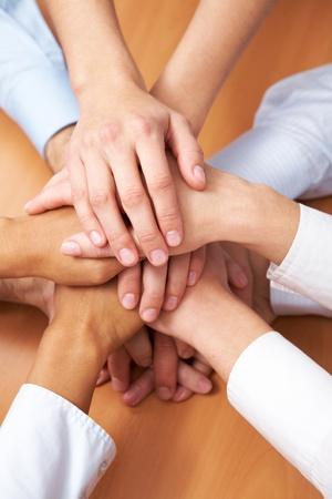 compa�erismo: Imagen de asociados de negocios de manos por encima de otros que simboliza el compa�erismo
