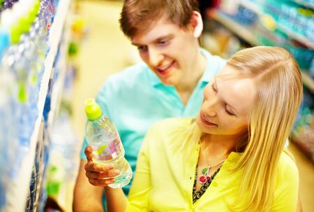 Image of happy couple choosing mineral water in supermarket photo