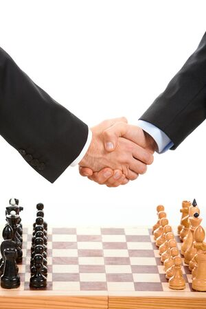 Image of chess-board with business handshake over it photo