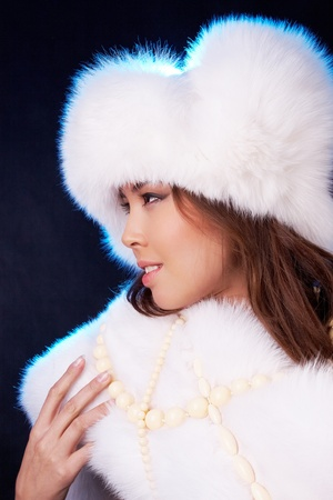 Profile of elegant young woman wearing white fur clothes  photo