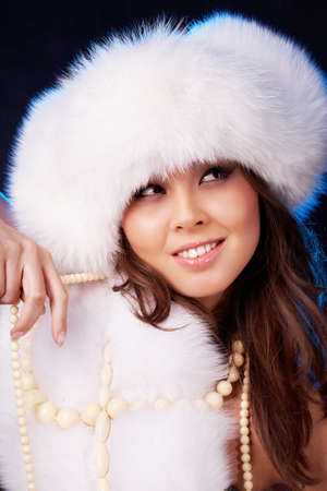Image of beautiful female in white luxurious fur clothes and white beads  photo
