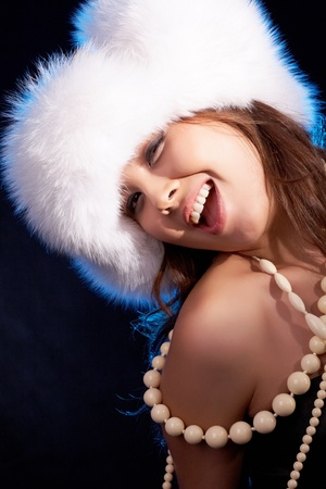 Portrait of joyful female in white luxurious cup and beads  photo