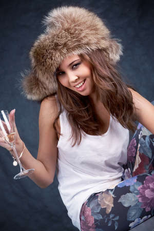 Image of drunk woman in luxurious fur cap holding flute of  champagne photo