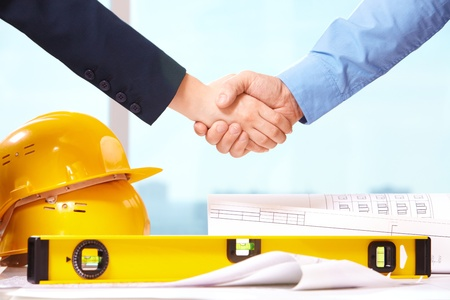 Close-up of business people handshaking over helmets, documents, worker tool  photo