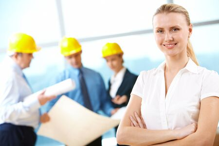 folding arms: Portrait of beautiful architect folding arms on the background of workers  Stock Photo