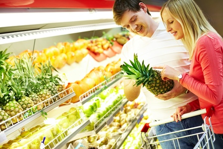 Portrait of healthy couple looking at fruits in supermarket during shopping Stock Photo - 9331614