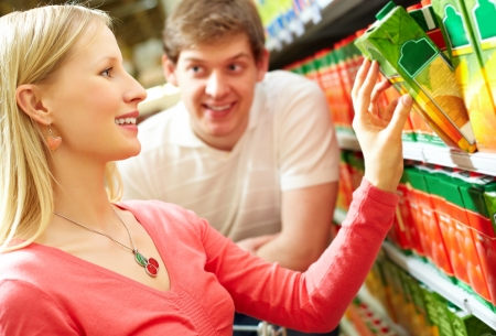 Portrait of happy girl choosing pack of juice in supermarket Stock Photo - 9331616