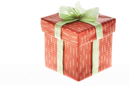 Isolated gift in decorative box bound with golden ribbon and bow on its top photo