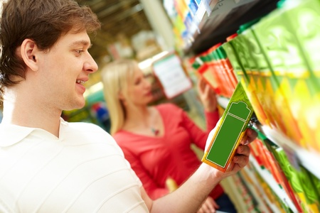 food sales: Portrait of happy man holding pack of juice in supermarket Stock Photo
