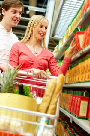 Portrait of young couple choosing pack of juice Stock Photo - 9331612