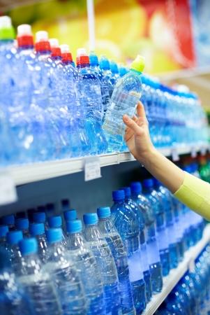 botellas de plastico: Primer plano de la botella de plástico de explotación femenina de agua mineral en una tienda