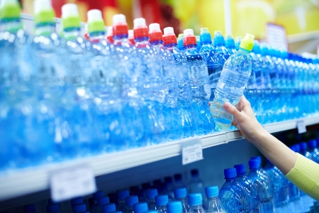 plastic container: Close-up of female choosing good mineral water in a shop Stock Photo