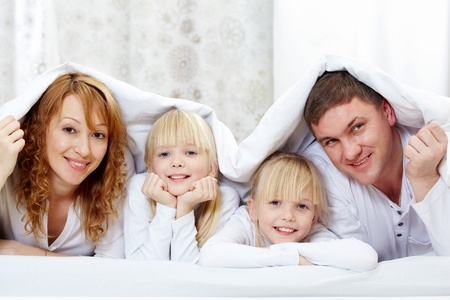 Portrait of cheerful family with twins lying under blanket    photo