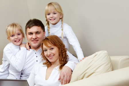 Portrait of cheerful family sitting on the sofa in the room    Stock Photo - 9352995