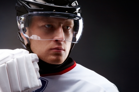 hockey player: Face of sportsman in protective helmet over black background