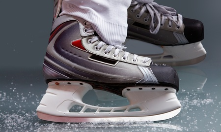 edge of the ice: Close-up of skates on player feet during ice hockey Stock Photo