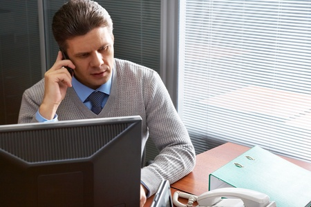 calling businessman: A serious manager talking on the phone in office