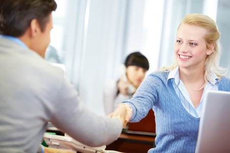 A young businessman and businesswoman shaking hands  photo