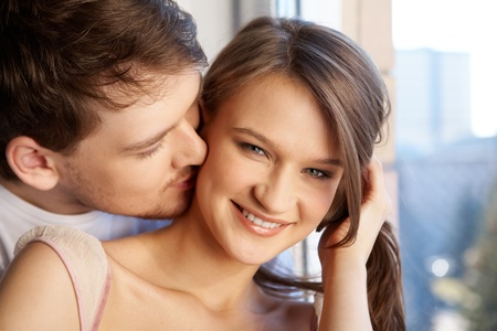 Close-up of young man kissing to woman�s cheek  photo