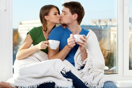passionate kissing: Close-up of young man and woman touching cup together  Stock Photo