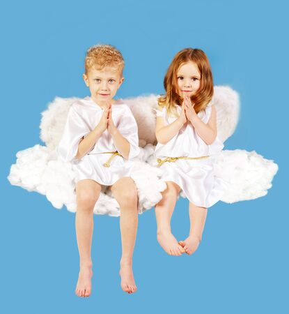Portrait of two cute angels sitting on the cloud  photo