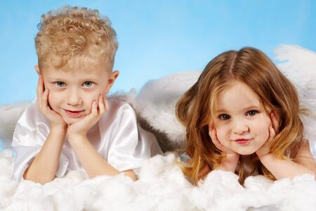Small boy and girl in angelic costume lying on white cloud  Stock Photo - 9353324