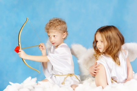 seraphic: Portrait of two cute cupids sitting on the cloud