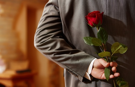 Photo of man in suit holding a red rose behind his back   photo