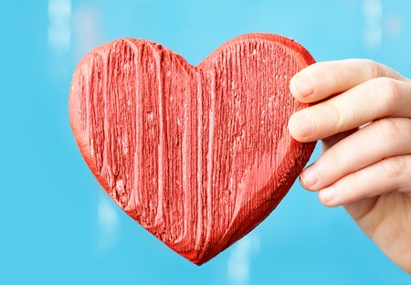 Close-up of female hand with a red wooden heart photo