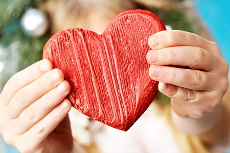 true love: Close-up of red wooden heart in child�s hands showing it