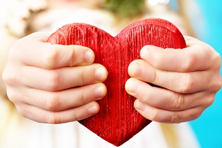 Girls hands showing a red wooden heart photo