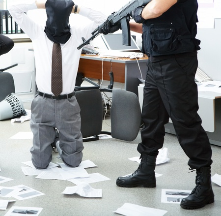 stealer: Photo of kneeling businessman wearing black sacks on head with burglar standing near by Stock Photo