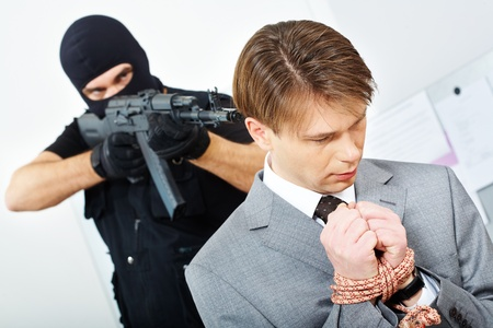 holding gun to head: Portrait of confused businessman with bound hands being chased by gangster pointing gun at him
