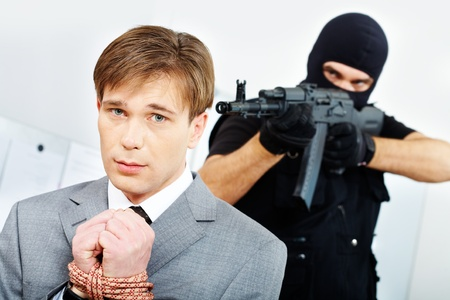 balaclava: Businessman with bound hands afraid gangster