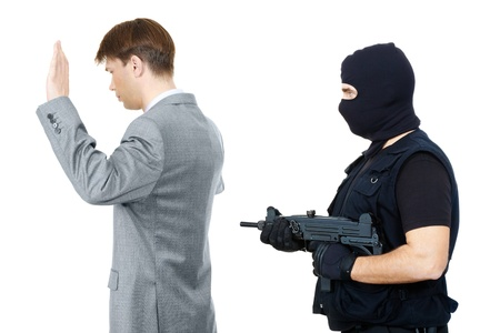 balaclava: Victim standing with hands raised while mafia representative pointing gun at them behind Stock Photo