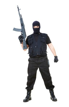 balaclava: Portrait of dangerous bandit in black wearing balaclava and holding gun in hand