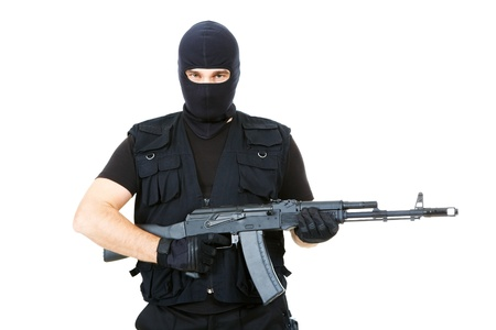 terrorists: Portrait of violent killer holding firearm and looking at camera with balaclava on his head