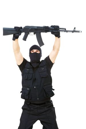 Portrait of armed assassin raising rifle in his hands over white background photo