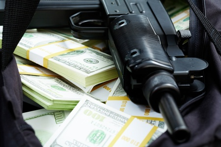 larceny: Close-up of black weapon lying on heap of hundred dollar bills