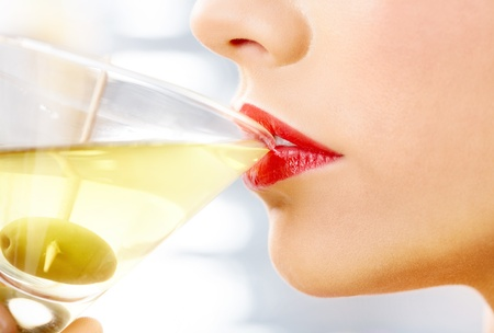 Close-up of woman drinking martini with olive  photo