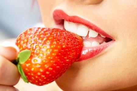 Photo of white teeth touching sweet strawberry  photo