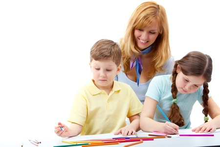 Portrait of children drawing pictures and teacher standing near     photo