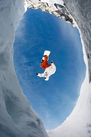 View from below of snowboarder jumping over rocky mountainside in winter photo