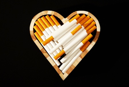 corazon: Cigarettes in heart shape against black background