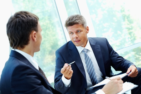 interview: Image of smart boss explaining to colleague business idea  Stock Photo