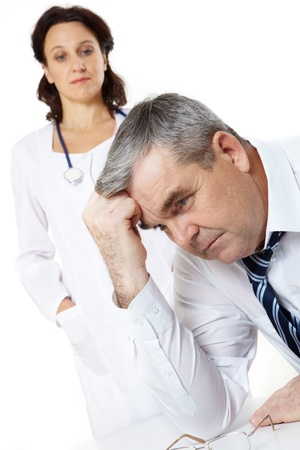 Portrait of a troubled senior man and a woman doctor photo