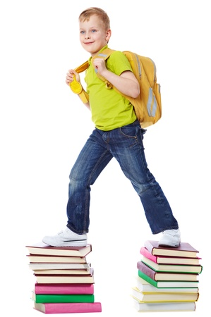 satchel: A boy with satchel walking on two heaps of books