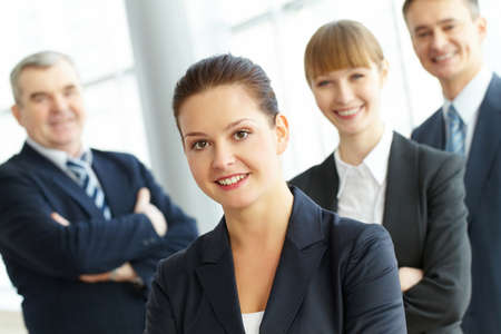 A young businesswoman smiling against her three colleagues   Stock Photo - 9402678