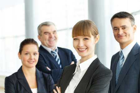 A young businesswoman smiling against her three partners  Stock Photo - 9402560